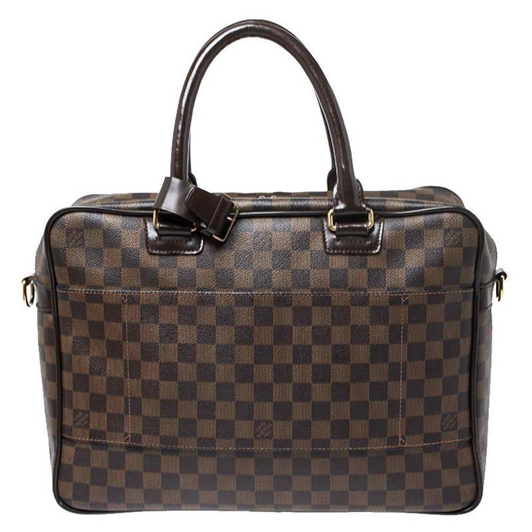 Smart and stylish, this Icare bag from Louis Vuitton deserves a special place in your closet! It is crafted from LV's signature Damier Ebene canvas and features dual top handles, a front zip pocket and a top zipper that opens to reveal a capacious