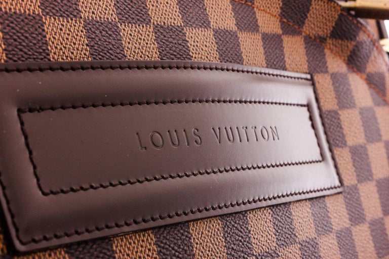Brown and tan Damier Ebene coated canvas Louis Vuitton Pegase with brass hardware, tan vachetta leather trim, single pocket at exterior, dual flat handles at exterior, single telescopic handle, brown canvas lining, single zip pocket and two-way all