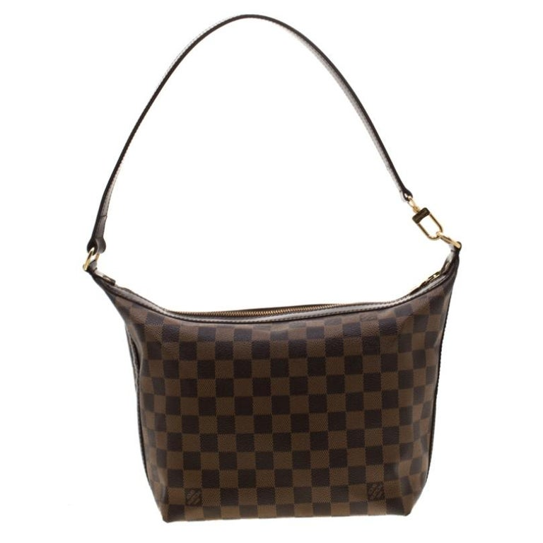 Elevate your look with this well crafted Louis Vuitton Portobello bag. Crafted from signature Damier Ebene canvas the bag comes with a top handle. The zipper pull opens to a canvas lined interior that has enough space to store your essentials. Lend