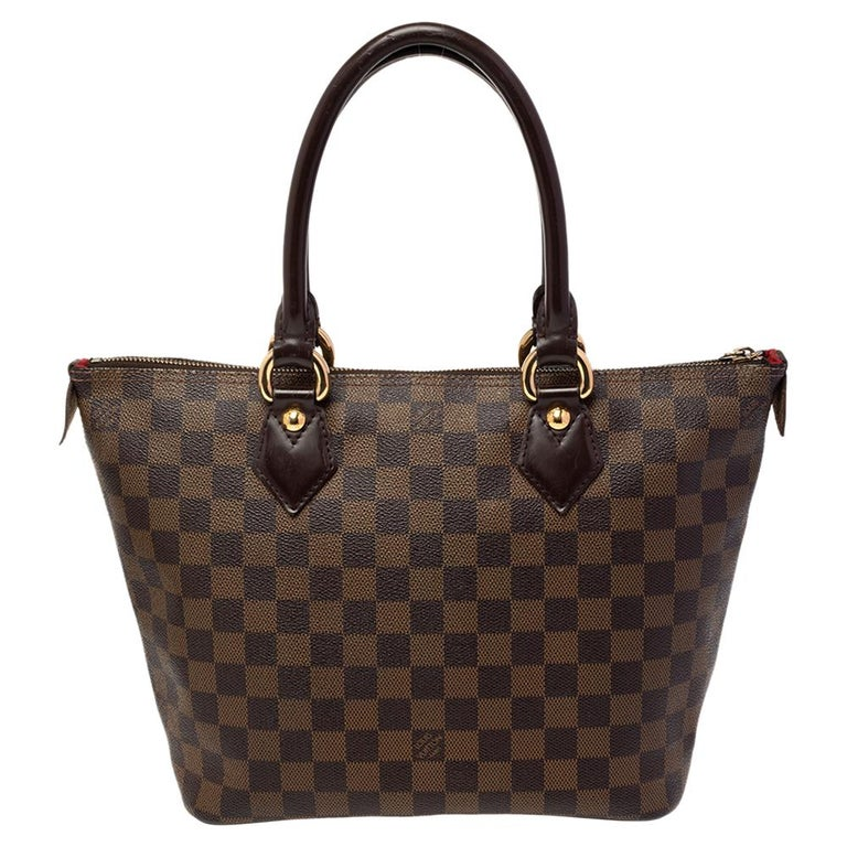 This Saleya PM by Louis Vuitton will add ease to your daily routine. Crafted from Damier Ebene canvas, it features a top zipper closure, dual handles, and polished gold-tone hardware. The Alcantara-lined interior has ample space for all your