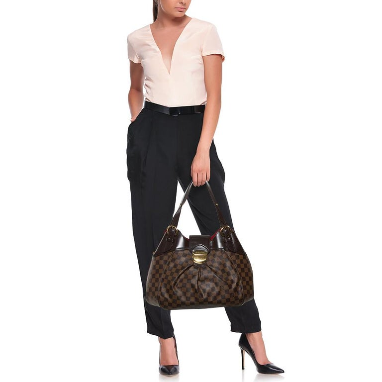 Louis Vuitton's handbags are famous for their high style, durability, and functionality. This Sistina bag, like all the other designs, is practical and stylish. Crafted from Damier Ebene canvas, the bag can be paraded using dual handles. It is