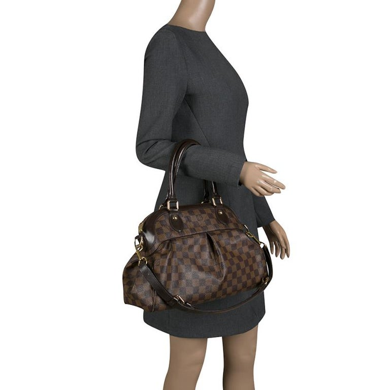 3501322bc05 This Trevi GM bag by Louis Vuitton has been crafted from Damier Ebene  canvas. It