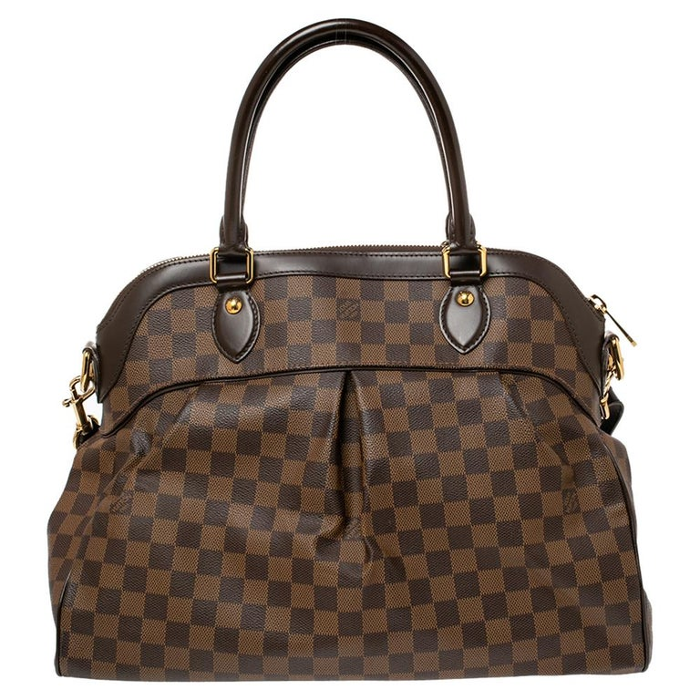 This Trevi bag by Louis Vuitton has been crafted from Damier Ebene coated canvas and it features two leather handles and a removable shoulder strap. It has gold-tone hardware, protective metal feet, and a top zip that opens up to a spacious