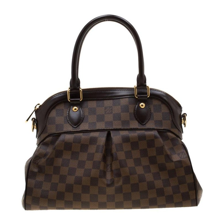 This Trevi bag by Louis Vuitton has been crafted from Damier Ebene canvas. It features dual leather handles, a removable shoulder strap, gold-tone hardware and protective metal feet at the bottom. The top zip closure opens up to a spacious Alcantara