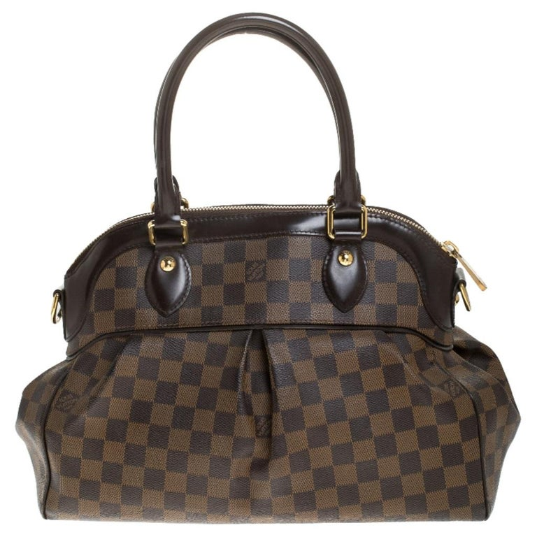 This Trevi bag by Louis Vuitton has been crafted from Damier Ebene coated canvas and it features two leather handles and a removable shoulder strap. It has gold-tone hardware, protective metal feet and a top zip that opens up to a spacious Alcantara