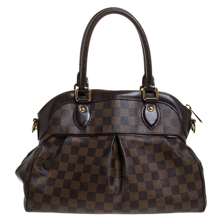 This Trevi bag by Louis Vuitton has been crafted from Damier Ebene canvas and it features two handles and a removable shoulder strap. It has gold-tone hardware, protective metal feet and a top zip that opens up to a spacious Alcantara compartment.