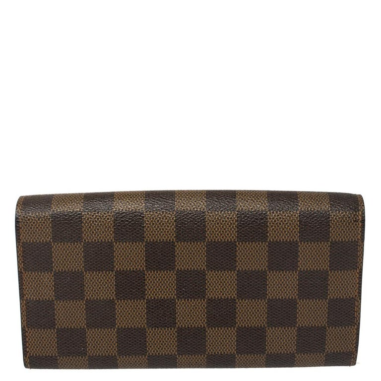 One of the most famous wallets by Louis Vuitton is the Sarah. This one here comes made from Damier Ebene canvas and the button on the flap opens to an interior with multiple card slots and a zip pocket. Perfect in size, this wallet can easily fit