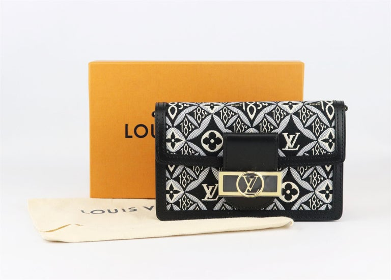 Louis Vuitton 'Dauphine' bag has the brand's signature 'Since 1854' canvas textile fabric on a wallet on chain with a slim detachable gold-tone chain, so you can carry it as a shoulder bag, made in Italy from black smooth leather trim, it's finished