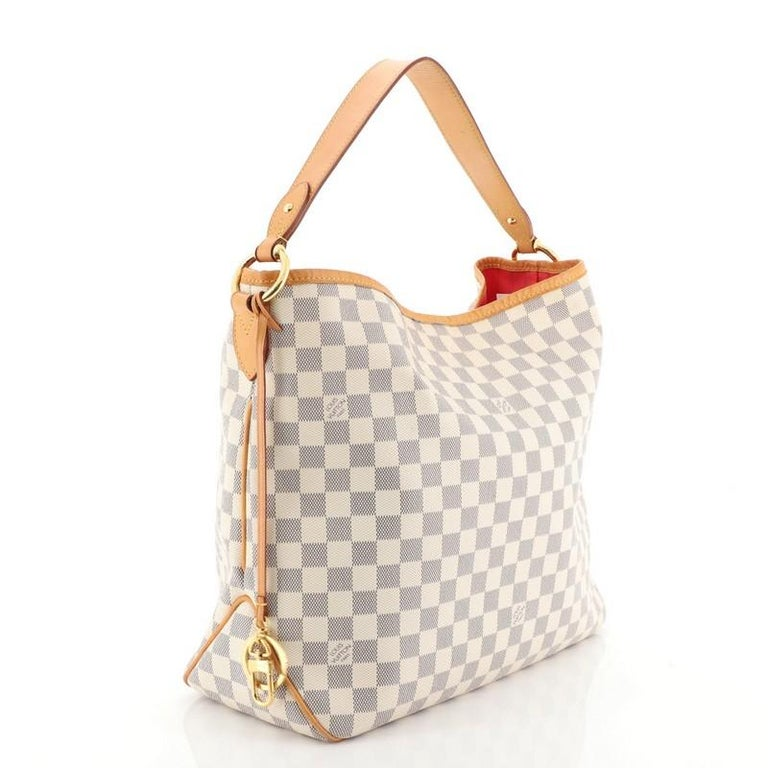 This Louis Vuitton Delightful NM Handbag Damier MM, crafted in damier azur coated canvas, features a flat leather handle and gold-tone hardware. Its hook closure opens to a pink fabric interior with side zip pocket. Authenticity code reads: MI2135.