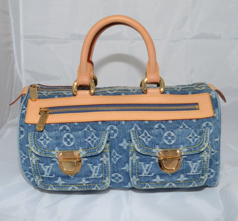 Louis Vuitton handbag featured in blue denim with a signature monogram design, top leather handles, zipper fastening, and two functional flap pockets at the front. Gold-tone hardware throughout. Interior is fully lined in a mustard-yellow suede