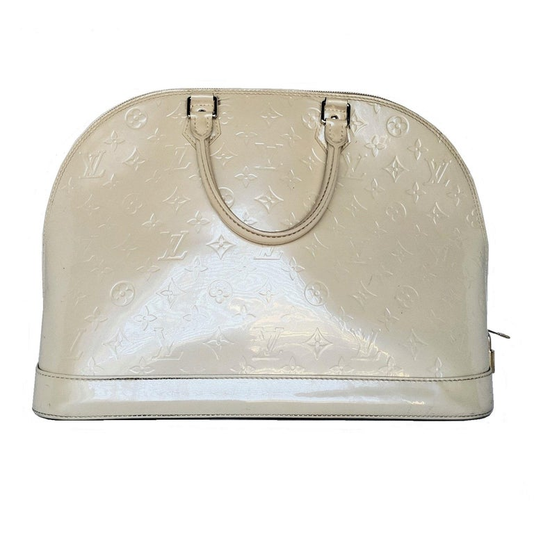 Dune Monogram Vernis leather Louis Vuitton Alma GM with brass hardware, dual rolled top handles, protective feet at base, tonal canvas lining, dual interior slit pockets and zip-around closure at exterior. Includes clochette, keys, padlock and dust
