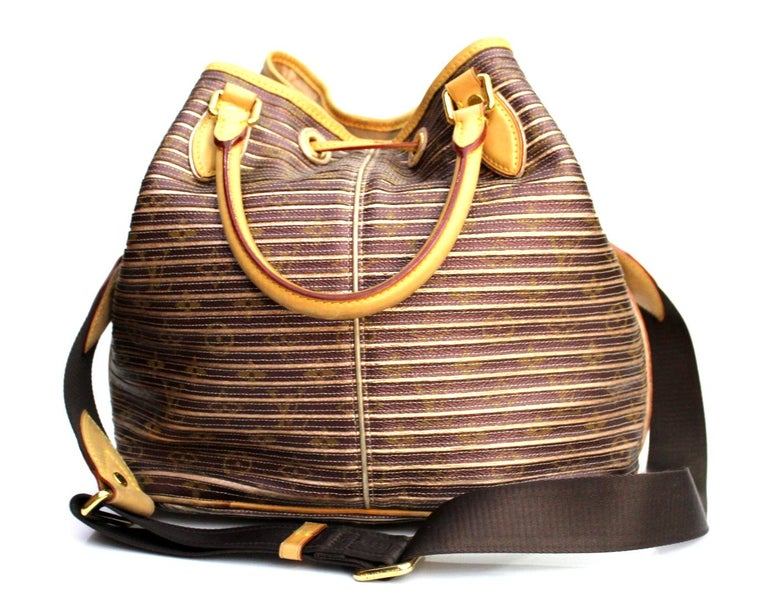 The Eden Neo Peche Monogram bag by Louis Vuitton is a unique and practical bag. The bag features a superimposition of Monogram metallic stripes. It has a drawstring closure in leather, upper handles and a canvas shoulder strap. You can carry this