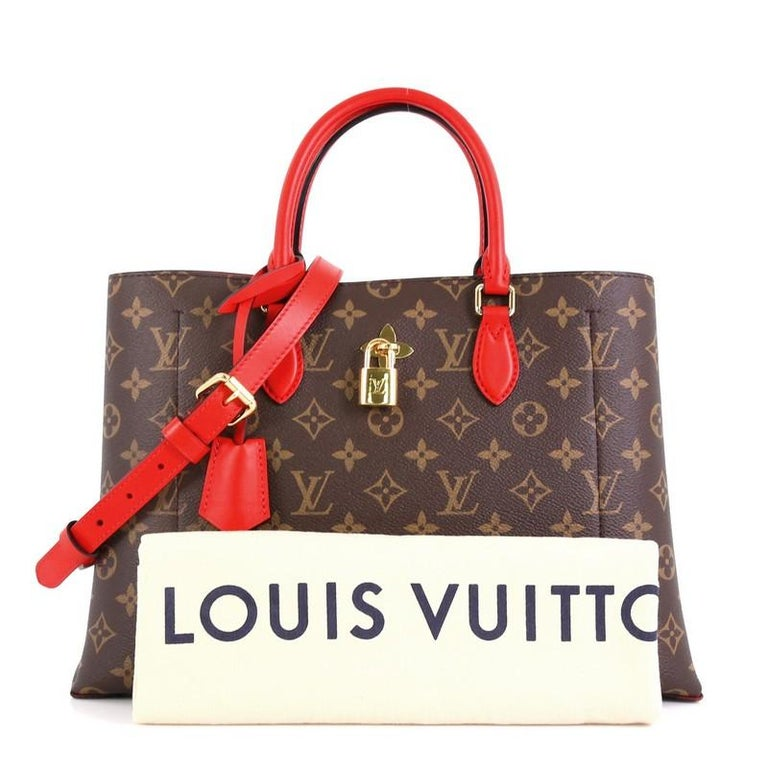 This Louis Vuitton Flower Tote Monogram Canvas, crafted in brown monogram coated canvas, features dual rolled leather handles, monogram flower padlock, and gold-tone hardware. It opens to a red microfiber interior with a center zip compartment and