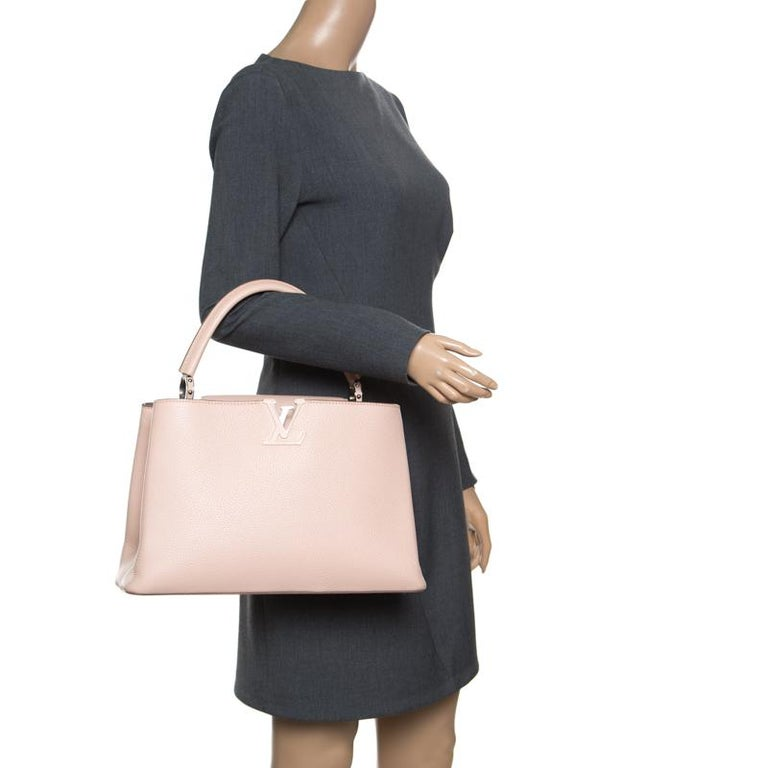 It is every woman's dream to own a Louis Vuitton handbag as appealing as this one. Crafted from Taurillon leather, this bag features a structured design with a single handle and protective metal feet. While the front LV elevate its beauty, the