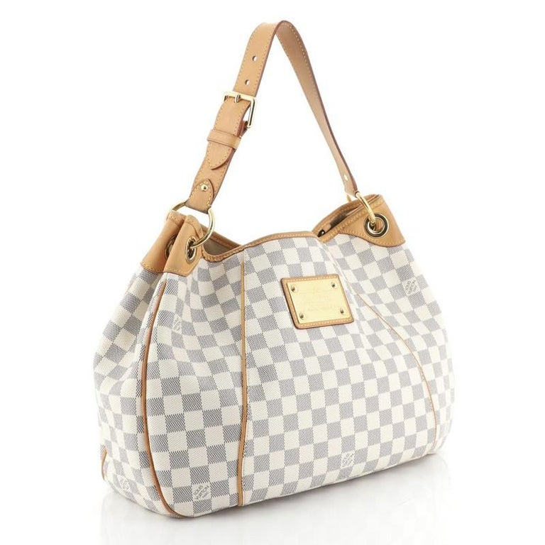 This Louis Vuitton Galliera Handbag Damier PM, crafted from damier azur coated canvas, features an adjustable shoulder strap, leather trim, metal logo plate, and gold-tone hardware. Its magnetic snap closure opens to a neutral microfiber interior