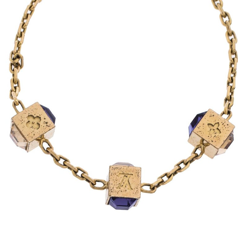 Artfully made from gold-tone metal, this flawless bracelet by Louis Vuitton can be your next prized possession. Featuring a gorgeous set of 3 cubes with monogram engravings and crystals, the design has been finished with the signature LV logo and a