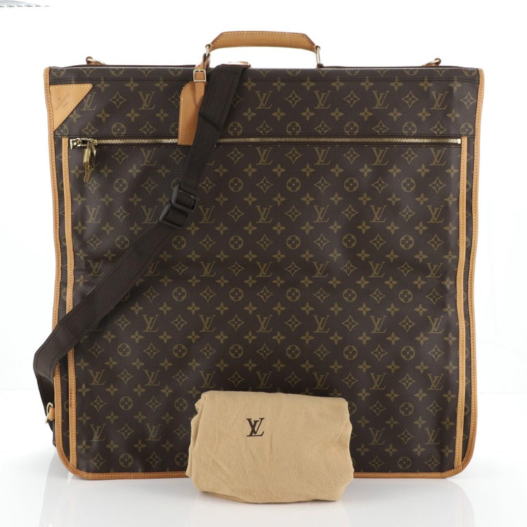 This Louis Vuitton Garment Carrier Bag Monogram Canvas Two Hangers, crafted in brown monogram coated canvas, features a top handle, front zip exterior compartments, side lock closures to keep the bag compact, hook at its base, and gold-tone