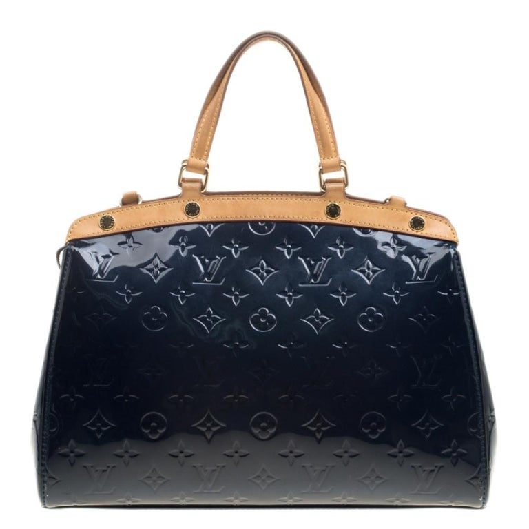 The feminine shape of Louis Vuitton's Brea is inspired by the doctor's bag. Crafted from their signature Vernis leather in grand blue, the bag has a perfect finish. The fabric-lined interior is spacious and it is secured by a zipper. The bag