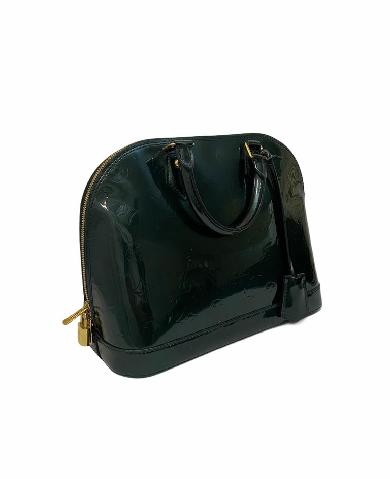 Louis Vuitton bag, Alma MM model, made of bottle green patent leather with golden hardware.  Equipped with a zip closure, internally lined in green canvas, quite roomy.  Present two rigid handles in paint, inside pockets and padlock with keys.  Good