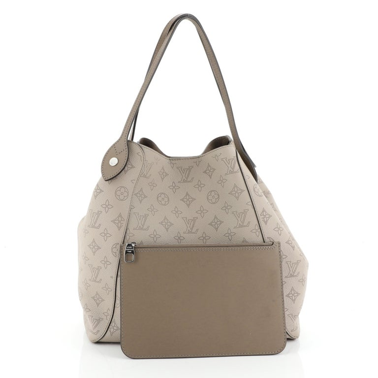 This Louis Vuitton Hina Handbag Mahina Leather MM, crafted from neutral mahina leather, features dual slim leather handles and silver-tone hardware. Its magnetic snap button closure opens to a neutral microfiber interior. Authenticity code reads: