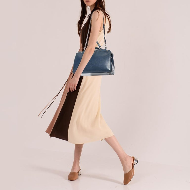The feminine shape of Louis Vuitton's Brea is inspired by the doctor's bag. Crafted from Epi leather, the bag has a perfect finish. The fabric interior is spacious and it is secured by a zipper. The bag features double handles, protective metal feet