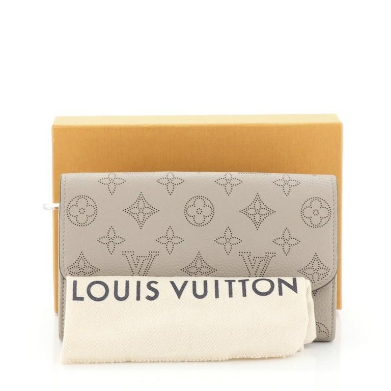 This Louis Vuitton Iris Wallet NM Mahina Leather, crafted from neutral mahina leather, features silver-tone hardware. Its snap button closure opens to a neutral leather interior with multiple card slots, middle zip pocket, and slip pocket.