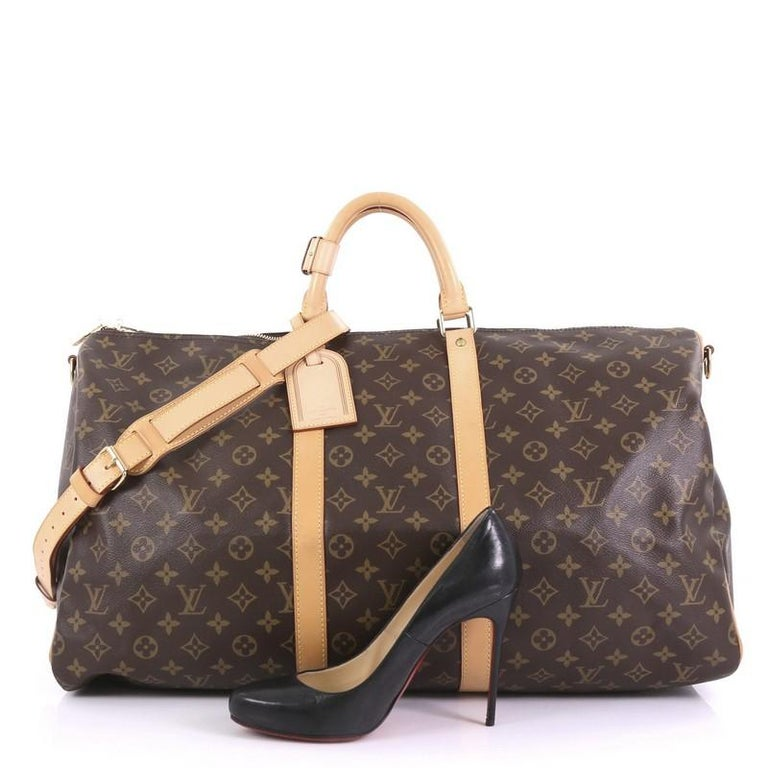 This Louis Vuitton Keepall Bag Monogram Canvas 55, crafted in brown monogram coated canvas, features dual rolled leather handles, vachetta leather trim, and gold-tone hardware. Its two-way zip closure opens to a brown fabric interior. Authenticity