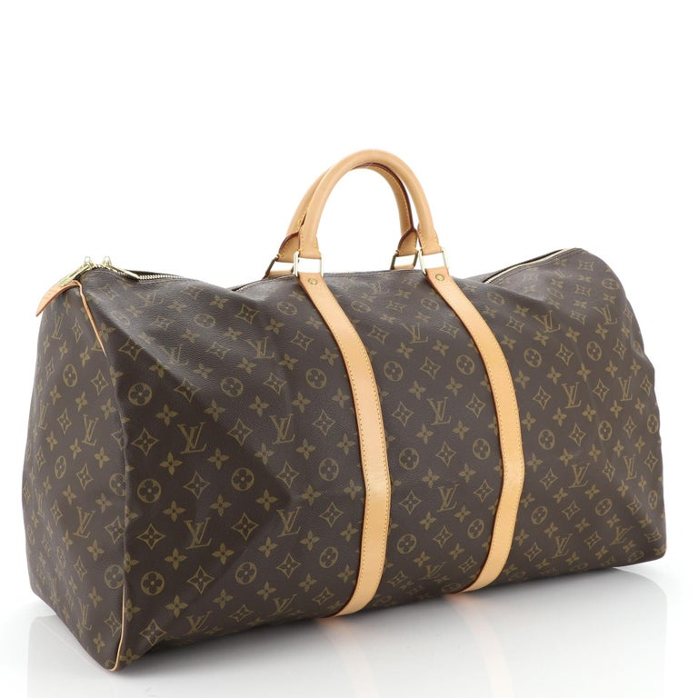This Louis Vuitton Keepall Bag Monogram Canvas 60, crafted in brown monogram coated canvas, features dual rolled leather handles, vachetta leather trim, and gold-tone hardware. Its two-way zip closure opens to a brown fabric interior. Authenticity