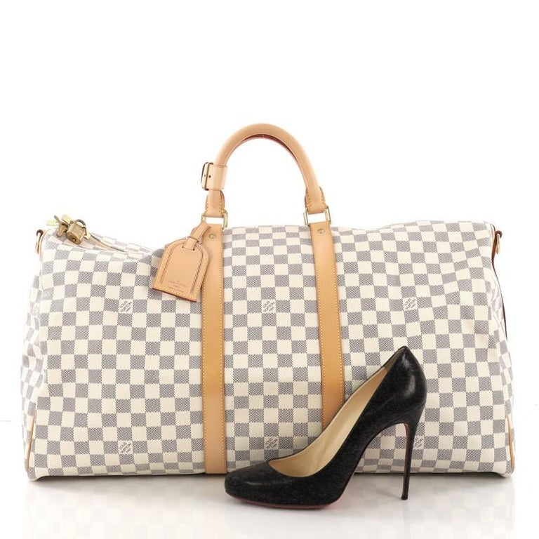 This Louis Vuitton Keepall Bandouliere Bag Damier 55 crafted from damier azur coated canvas, features dual rolled handles, leather trim, and gold-tone hardware. Its two-way top zip closure opens to a beige fabric interior. Authenticity code reads: