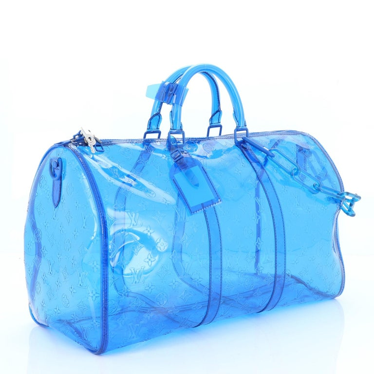 This Louis Vuitton Keepall Bandouliere Bag Limited Edition Monogram PVC 50, crafted in blue PVC, features dual rolled handles, resin chain, and silver-tone hardware. Its zip closure opens to a black PVC interior. Authenticity code reads: BA4168.