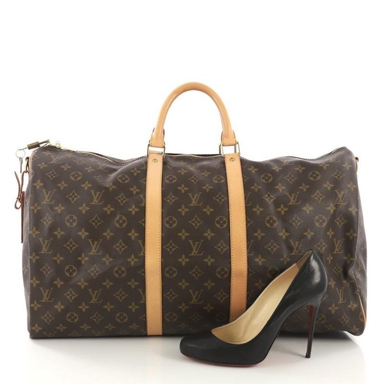 This Louis Vuitton Keepall Bandouliere Bag Monogram Canvas 55, crafted from brown monogram coated canvas, features dual rolled handles, natural cowhide leather trims, and gold-tone hardware. Its zip closure opens to a brown fabric interior.