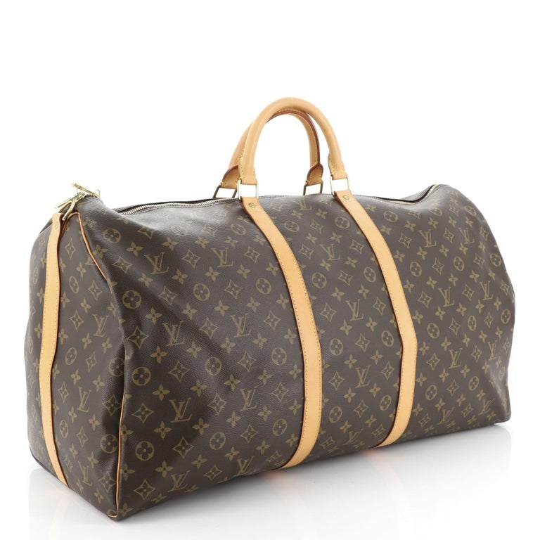 This Louis Vuitton Keepall Bandouliere Bag Monogram Canvas 60, crafted from brown monogram coated canvas, features dual rolled handles, cowhide leather trim, and gold-tone hardware. Its zip closure opens to a brown fabric interior. Authenticity code