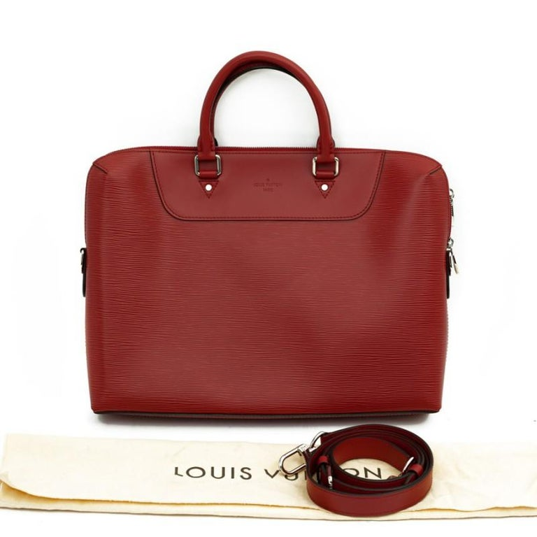 This Louis Vuitton document holder is in Epi brick leather. The jewelry is silver metal with double zipper. It can be carried by hand or on the shoulder with its strap. It is lined in dark suede, a large storage space and several flat pockets