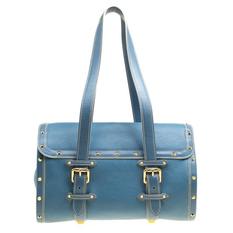 This L'Epanoui GM bag from Louis Vuitton is gorgeous. The beauty in alight blue hue is crafted from leather and flaunts a unique and distinctive style. It features beautiful gold-tone studs outlining the bag in an orderly fashion, a push lock