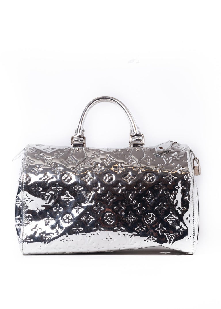 This limited edition Louis Vuitton Speedy 35 bag is made with a shiny silver monogram mirrored vinyl exterior with patent leather trim. This celebrity-coveted bag has woven fabric interior lining with two slip pockets.