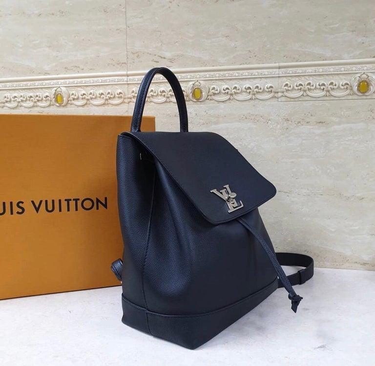 Black leather Louis Vuitton Lockme backpack with silver-tone hardware, single rolled top handle, dual flat adjustable shoulder straps, foil-stamped logo at exterior back, tonal Alcantara lining, single interior slit pocket and drawstring closure