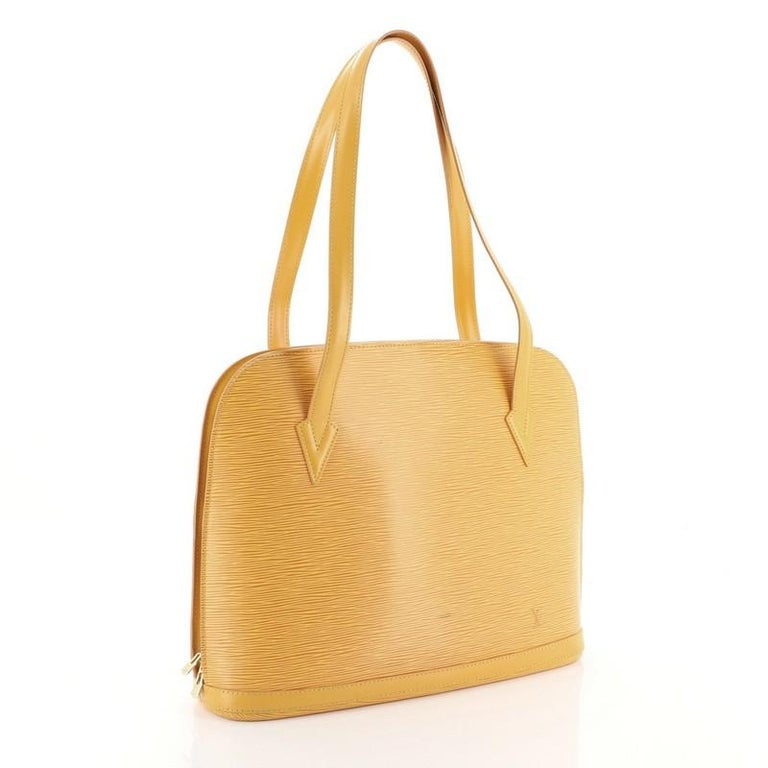This Louis Vuitton Lussac Handbag Epi Leather, crafted in yellow epi leather, features dual flat leather straps, subtle LV logo, and gold-tone hardware. Its two-way zip closure opens to a purple microfiber interior with zip and slip pockets.