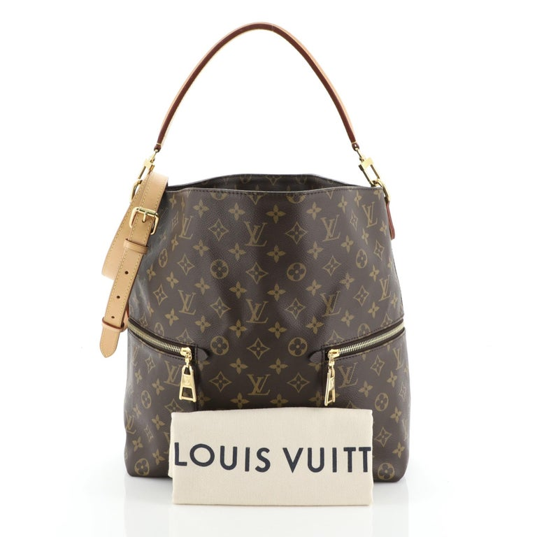 This Louis Vuitton Melie Handbag Monogram Canvas, crafted in brown monogram coated canvas, features a single looped leather handle, two exterior side zip pockets, and gold-tone hardware. It opens to a red microfiber interior with slip pockets.