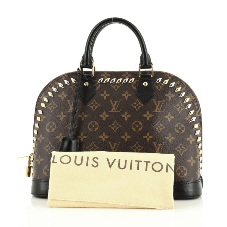 This Louis Vuitton Metal Stones Alma Handbag Studded Monogram Canvas PM, crafted from brown monogram coated canvas, features dual rolled handles, multiple studs, and silver and gold-tone hardware. Its zip closure opens to a brown fabric interior