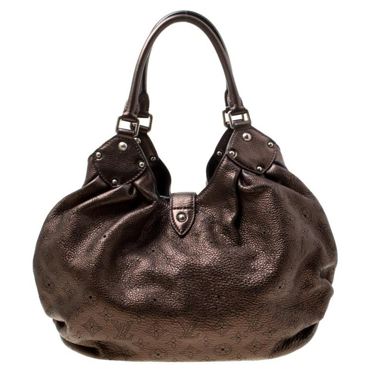 This hobo from the house of Louis Vuitton is a delight to own. Louis Vuitton's Mahina collection was inspired by the crescents of the moon. Featuring a slightly slouchy silhouette the bag comes with dual rolled top handles, buckle detailing on the