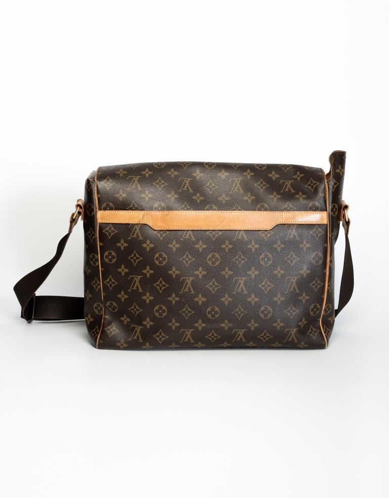 This bag is made with brown monogram canvas, vachetta leather trim and an adjustable woven shoulder strap with logo. Featuring a single exterior pocket, brass hardware, a large flap with pull through closure and brown woven fabric interior lining
