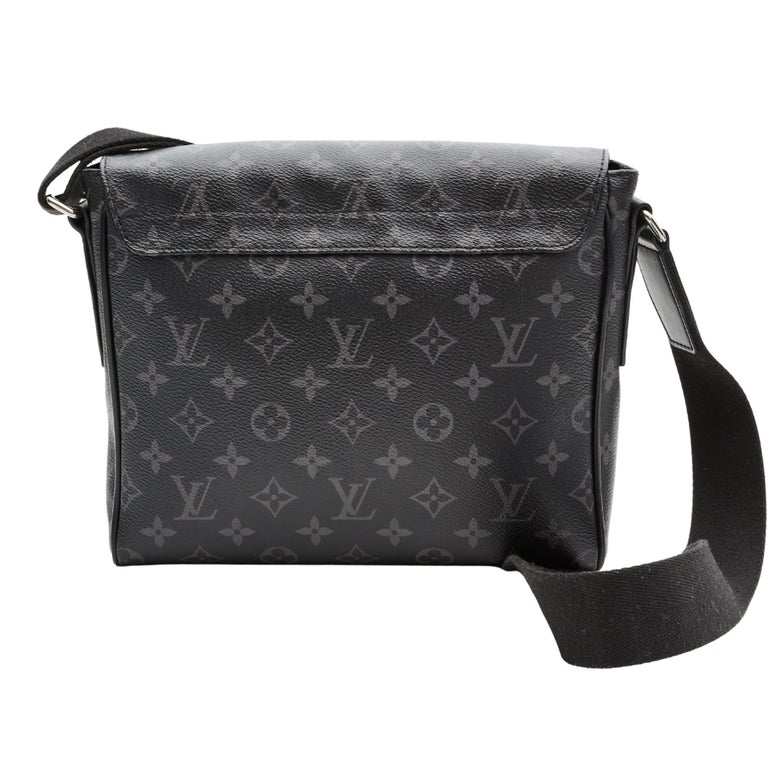 This bag is made with monogram print on toile canvas in graphite with black piping trim. The bag features an adjustable black crossbody strap, polished silver hardware, a front flap with a black Louis Vuitton LV logo and the bag opens to a black
