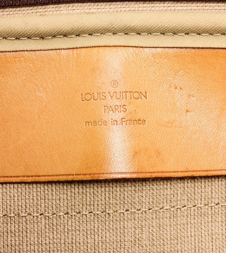 Brown and tan monogram coated canvas Louis Vuitton Alize 2 Poches with brass hardware, tan vachetta leather trim, luggage tag, dual rolled top handles, beige canvas lining, dual interior compartments, single open pocket at interior wall and dual zip