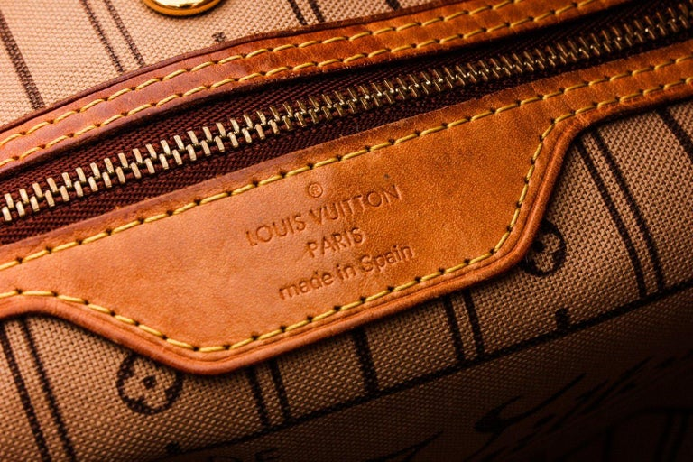 Brown and tan monogram coated canvas Louis Vuitton Neverfull MM with brass hardware, tan vachetta leather trim, dual flat shoulder straps, dual drawstring adornments at sides, striped canvas lining, single zip pocket at interior wall and clasp