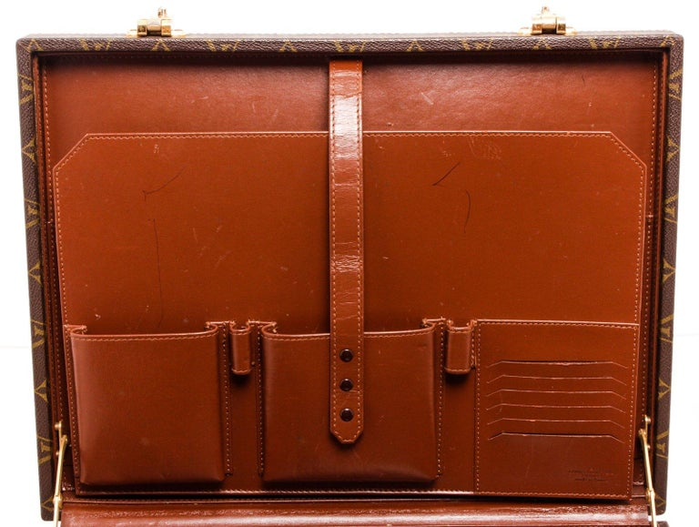 Louis Vuitton brown Monogram coated canvas President Briefcase with gold-tone hardware, brown leather interior, large back slip pocket, dual slip pockets, dual pen slots, and 6 card slots, push-lock closure.  25287MSC