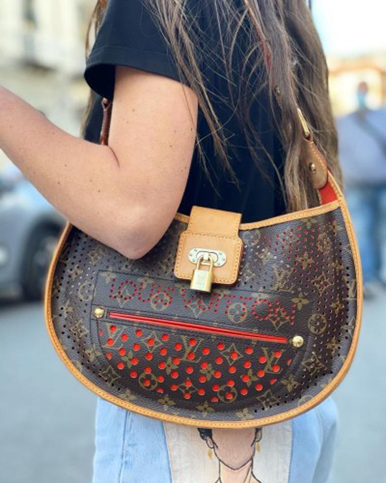 Louis Vuitton Perforated model bag made of monogram canvas with cowhide details, golden hardware and orange interior. Equipped with adjustable handle. Closure with hook, internally quite large. The bag is in good condition.  Dimensions: 5 × 32 × 25