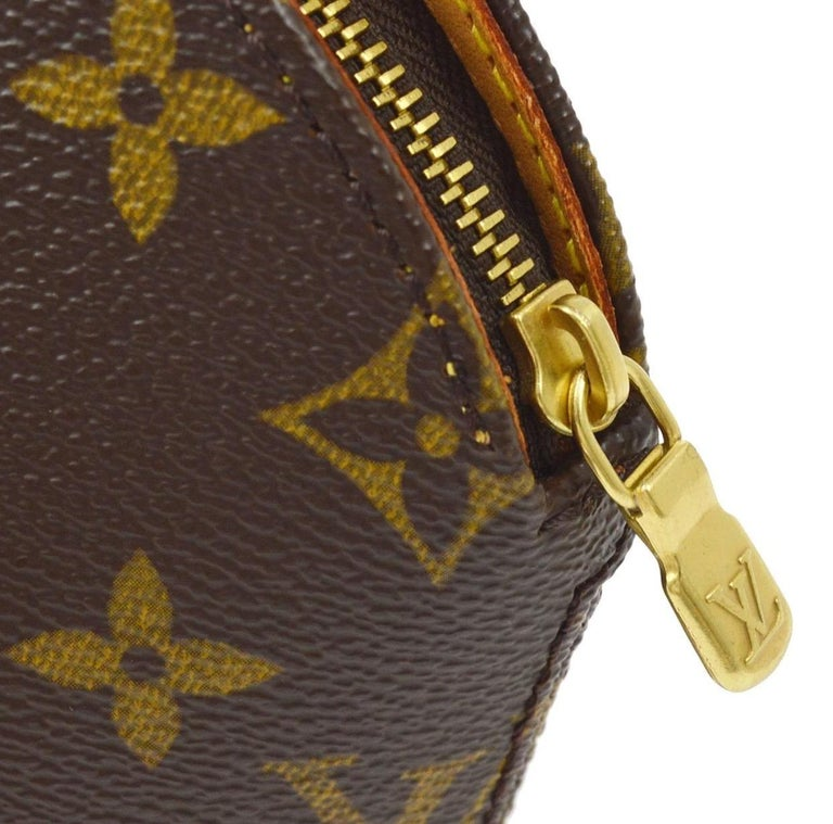 Monogram canvas Leather Gold tone hardware Woven lining Zipper closure Date code present Measures 4.25