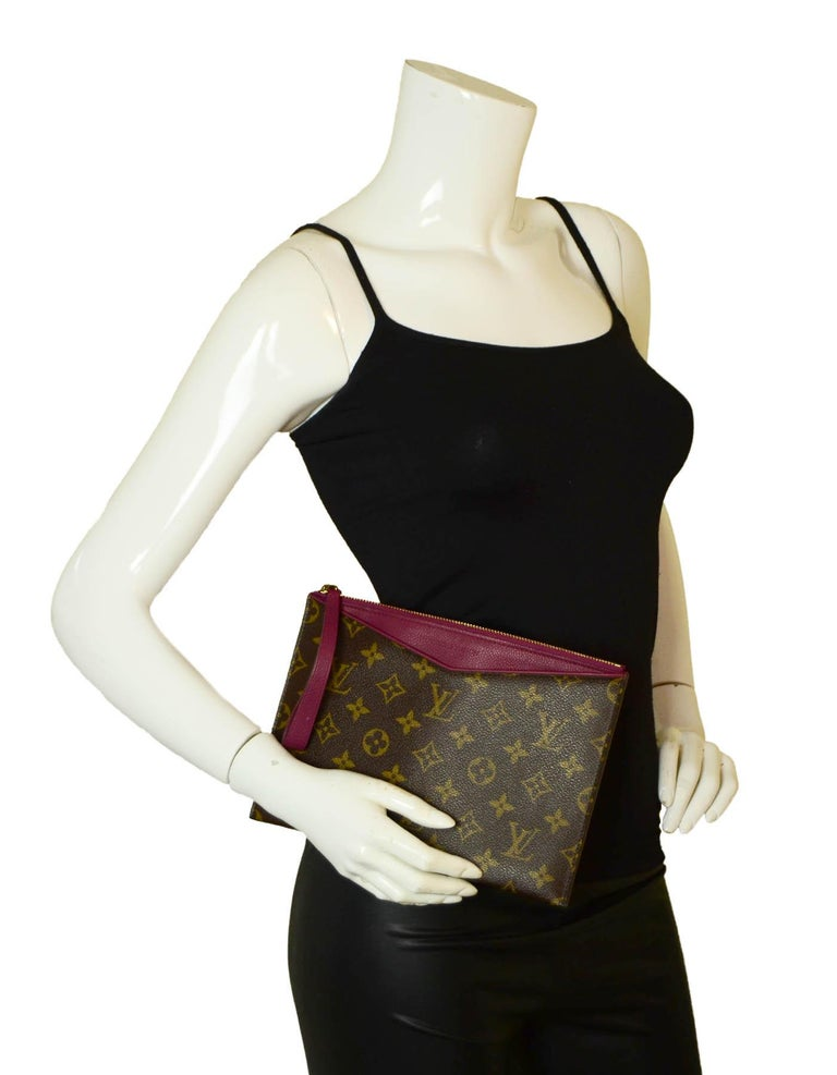 Louis Vuitton Monogram/ Grape Pochette Pallas Wristlet Bag  Made In: France Year of Production: 2014 Color: Brown with magenta trim Hardware: Goldtone Materials: Coated canvas and leather Lining: Leather Closure/Opening: Zip top Exterior Pockets: