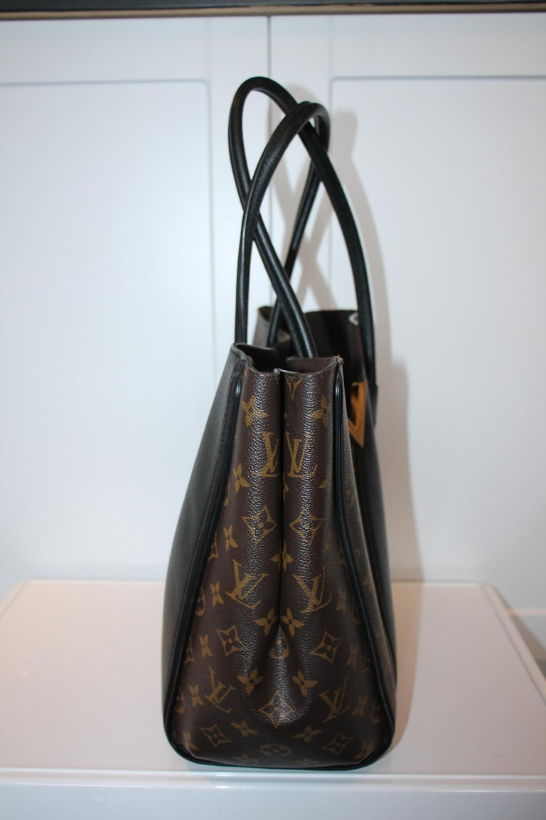 Brown and tan monogram coated canvas. Brass hardware. Clasp closure at top. Dual rolled shoulder straps. V logo embellishment and foil-stamped logo at front. Black leather panels throughout exterior. Protective feet at base. Chocolate Alcantara