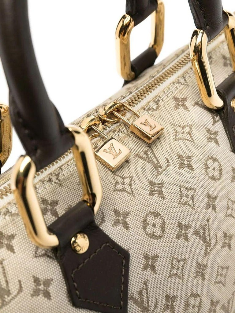 This unique version of a Louis Vuitton tote features several twists on a classic top-handle tote bag. Its elegantly elongated silhouette is crafted in beige-toned monogrammed canvas, accented by thick gold-tone hardware and a contrast brown leather